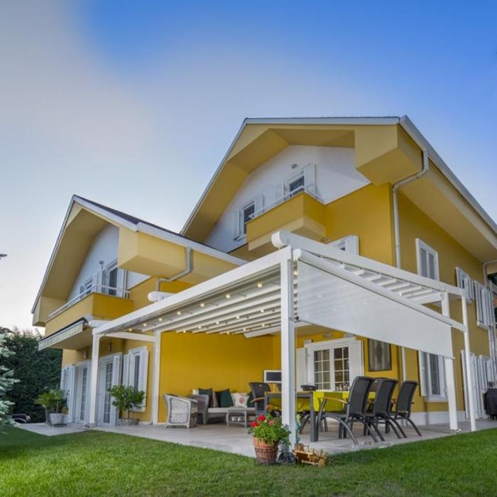pergola silver palmiye terrassenueberdachung gelbes Haus B 700x700 - PALMIYE - eine Geschichte mit Erfolg - ÜBER UNS